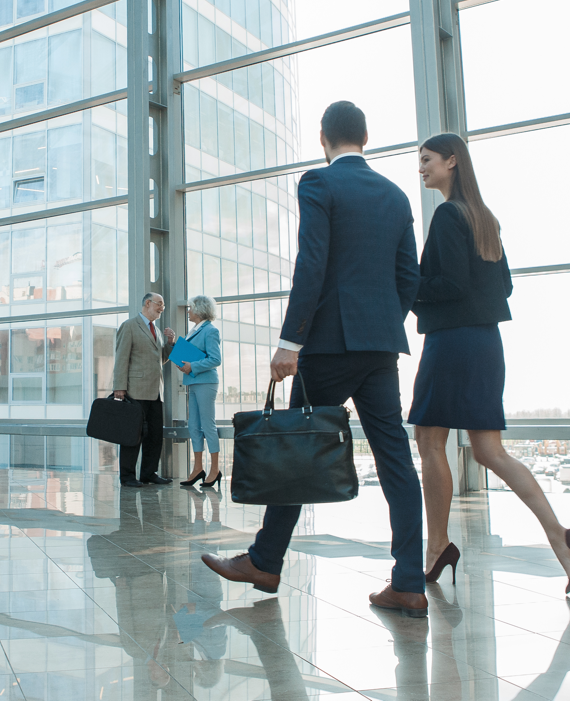 businessman and business woman walking in front of glass windows